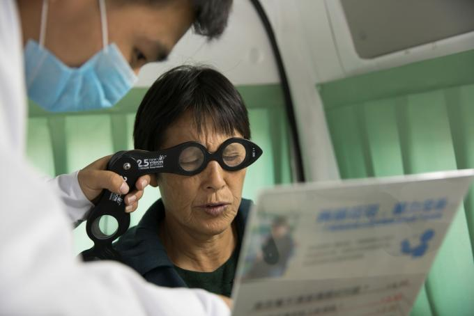 A man testing new glasses for women holding a newspaper