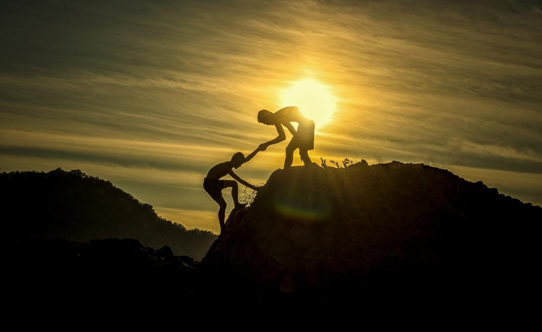 One person helping another to get up a rock