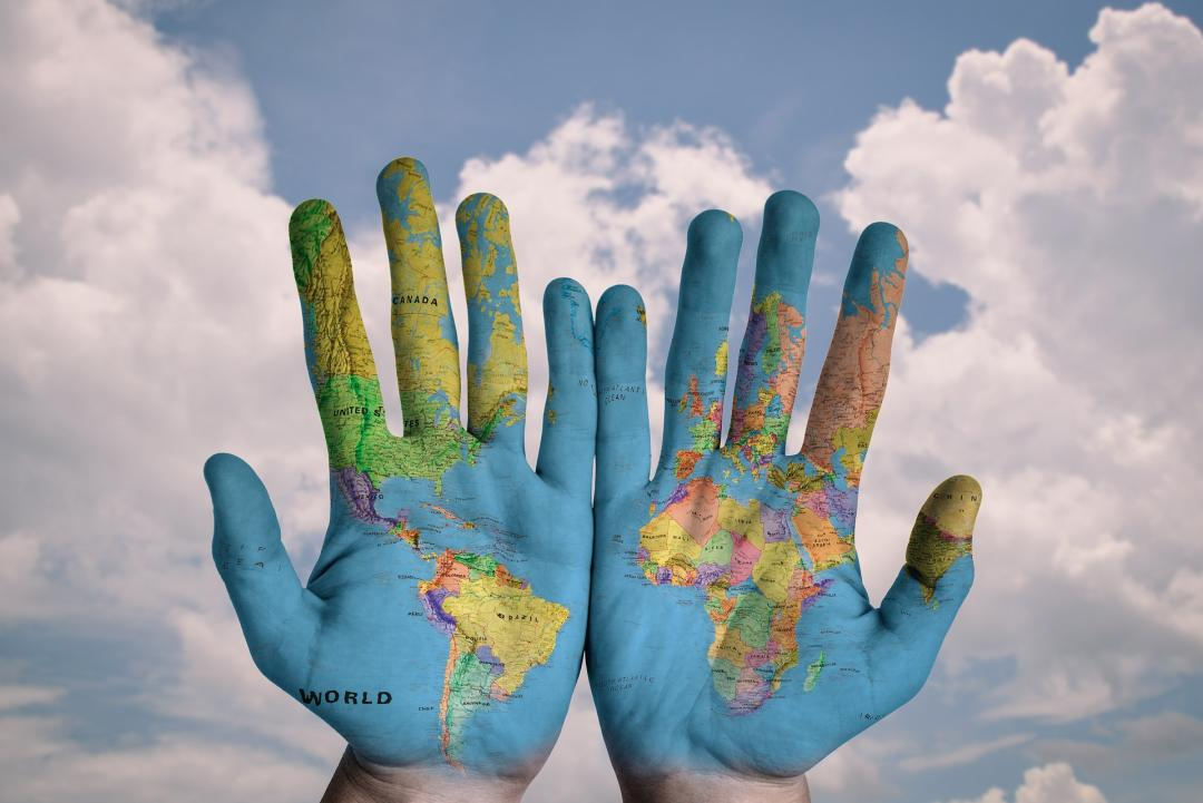 A pair of hands with the world map