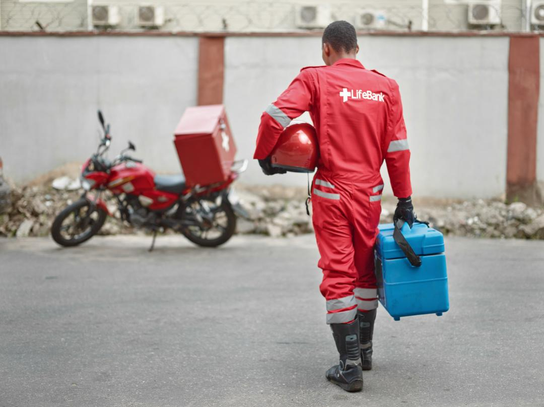 Life Bank employee carrying medical supply to a motorbike