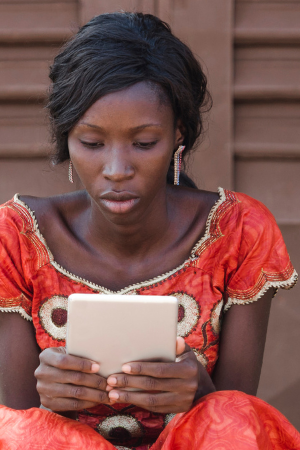 Street Shot of an African young woman working on business holding her tablet in a university in Bamako, Mali