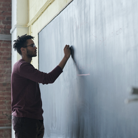 Man writing on a blackboard