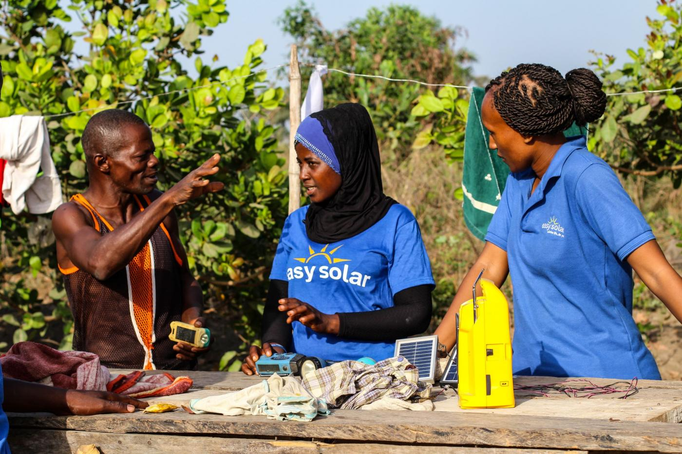 two women and a man with an off-grid solar panel
