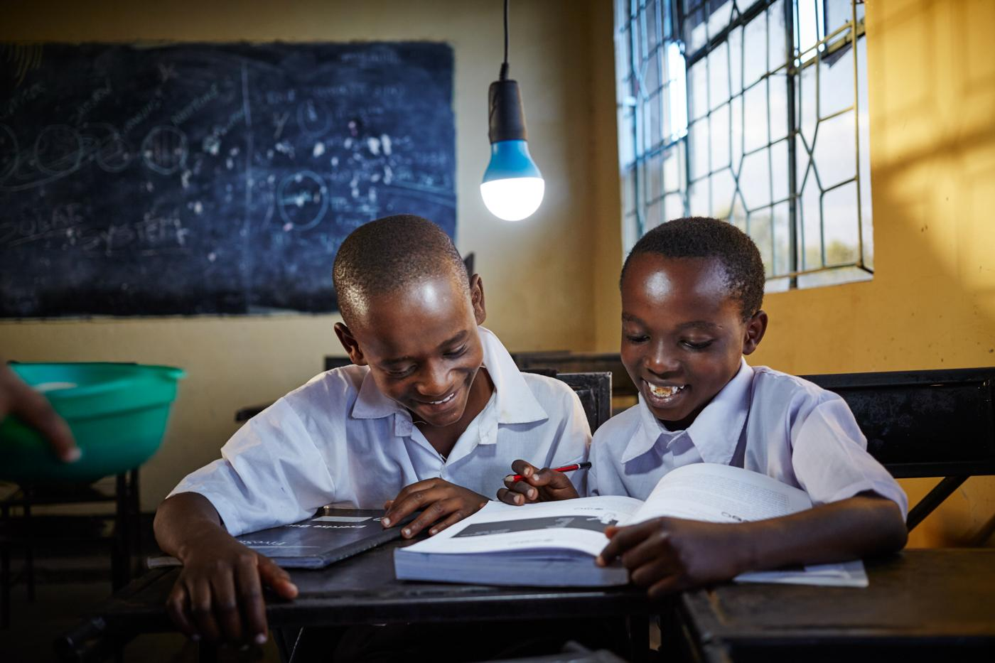 Zola Tanzania Solar Power Light bulb and pupils reading with