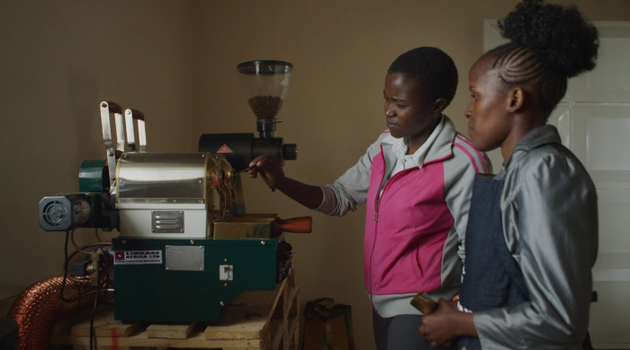 Two women with a coffee roasting machine