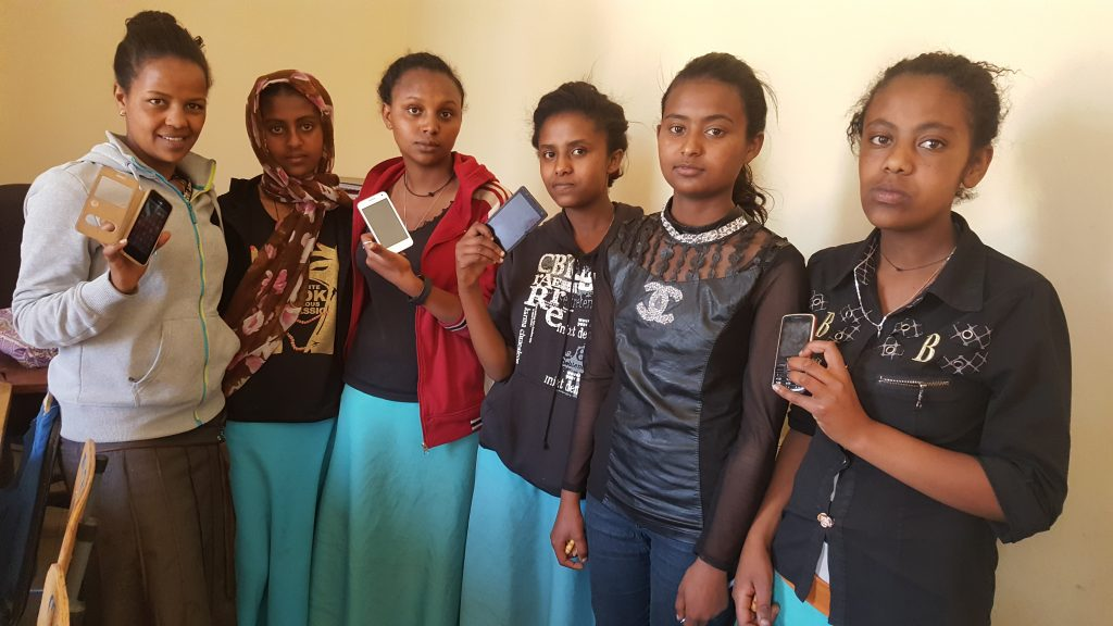 Ethiopian girls showing their mobile phones