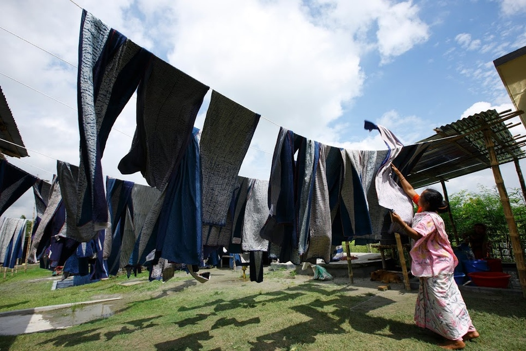 Step 14: An artist helps clothes to be dried in the open