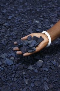 A processor holds a handful of sundried indigo
